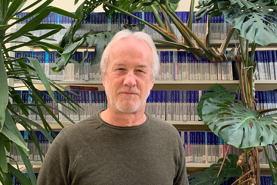 Foto von Herrn Neumann vor Bücherregal umrahhmt von großen Pflanzen