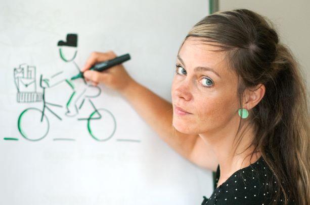 Claudia Ratering am Whiteboard ein Fahrrad zeichnend