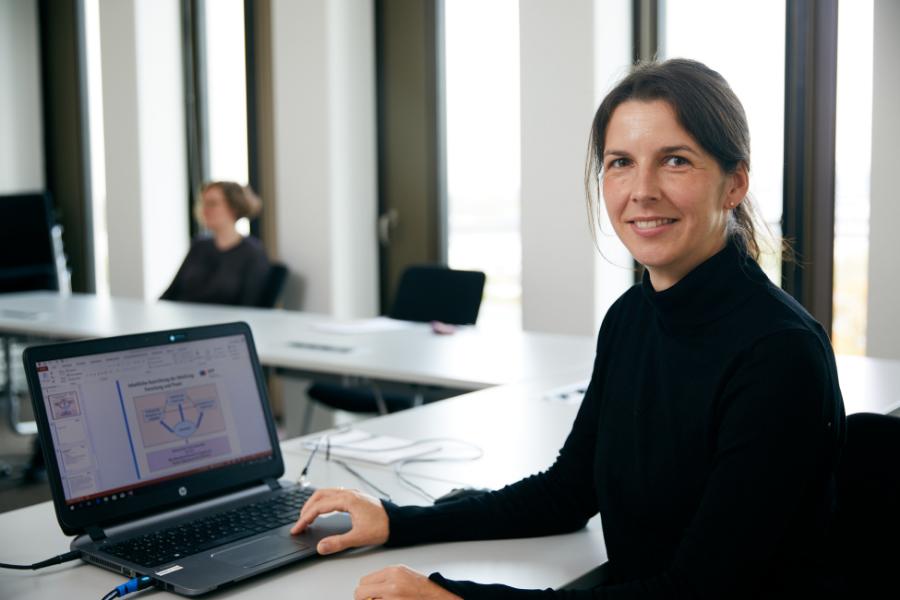 Halbporträt Urlike Hartmann, vor Laptop am Tisch sitzend